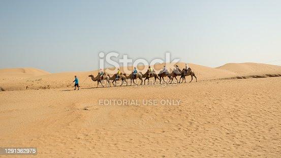 Kubuqi Desert, Inner Mongolia province / China - July 31, 2016: Guide taking tourists on two-humped Bactrian Camels in Kubuqi desert in northern China