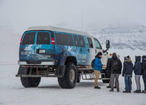 guide im gespräch mit touristen warten in lin in einem schweren modifizierten van auf dem weg zu eishöhlen zu bekommen - chevy van stock-fotos und bilder