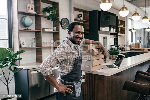 Portrait of smiling entrepreneur in coffee shop with the boxes