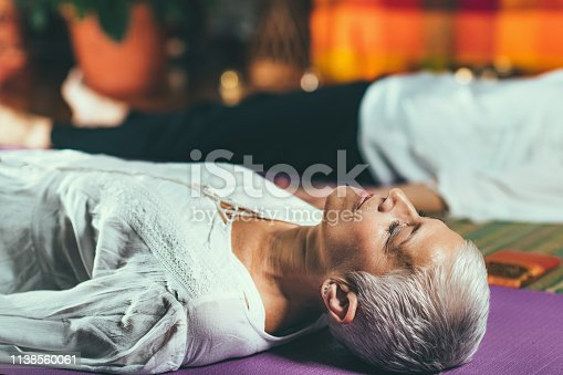 Guided meditation therapy. Senior woman meditating, lying on the floor