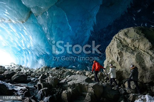 Guide and guests exploring a stunning glacial ice cave