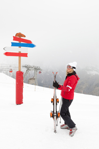First snow. .  Peaks in the Alps. Woman skiier at the guidepost