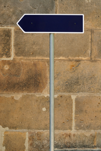 Guidepost in front of a sandstone wall
