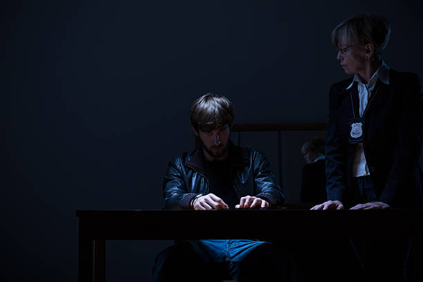 Guilty man and policewoman Guilty man and elderly policewoman in dark room police interview stock pictures, royalty-free photos & images