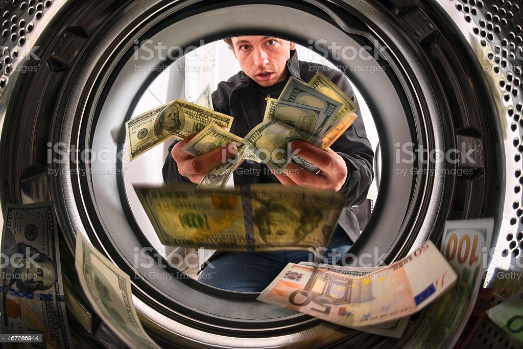Guilty man throwing money inside a washing machine stock photo