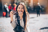 Smiling young businesswoman eating chocolate outdoors in the city