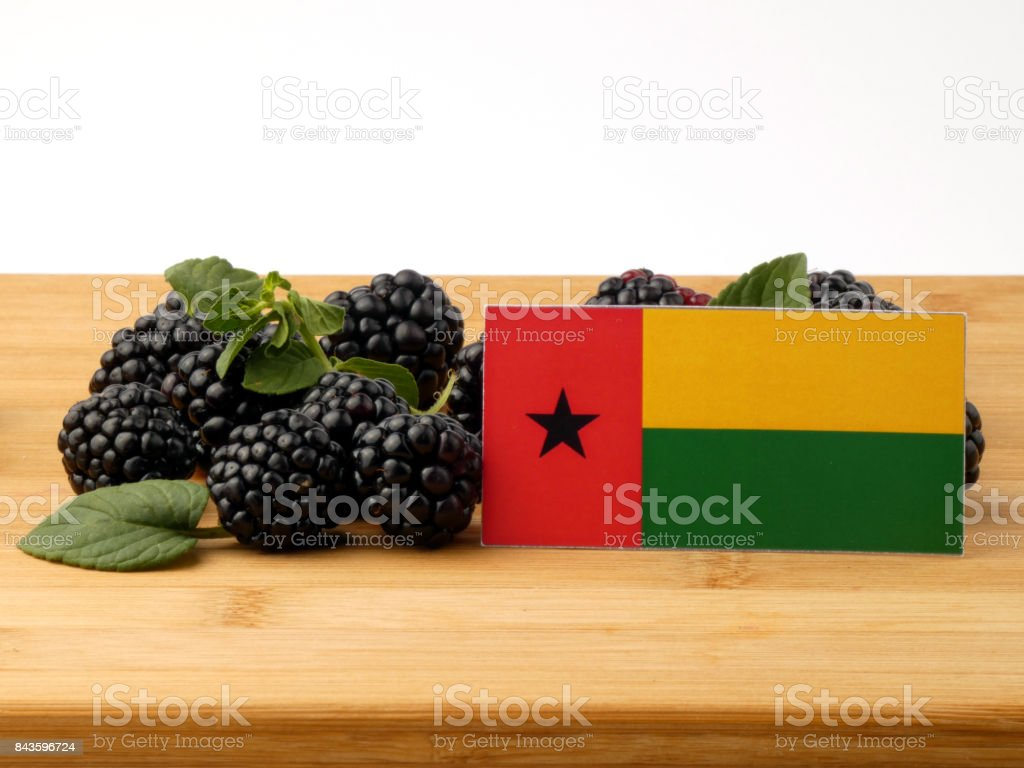 Guinea Bissau flag on a wooden panel with blackberries isolated on a white background stock photo