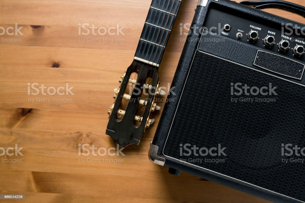 Guitar amplifier and old classical guitar on wood table stock photo