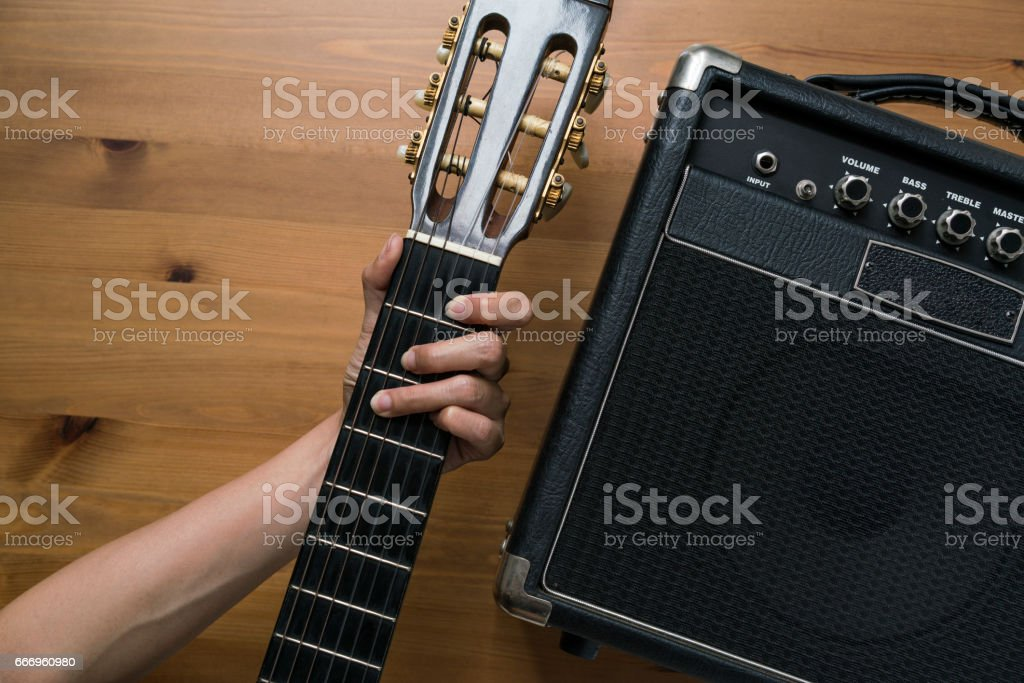 Guitar amplifier and woman hand holding a guitar on wood table stock photo