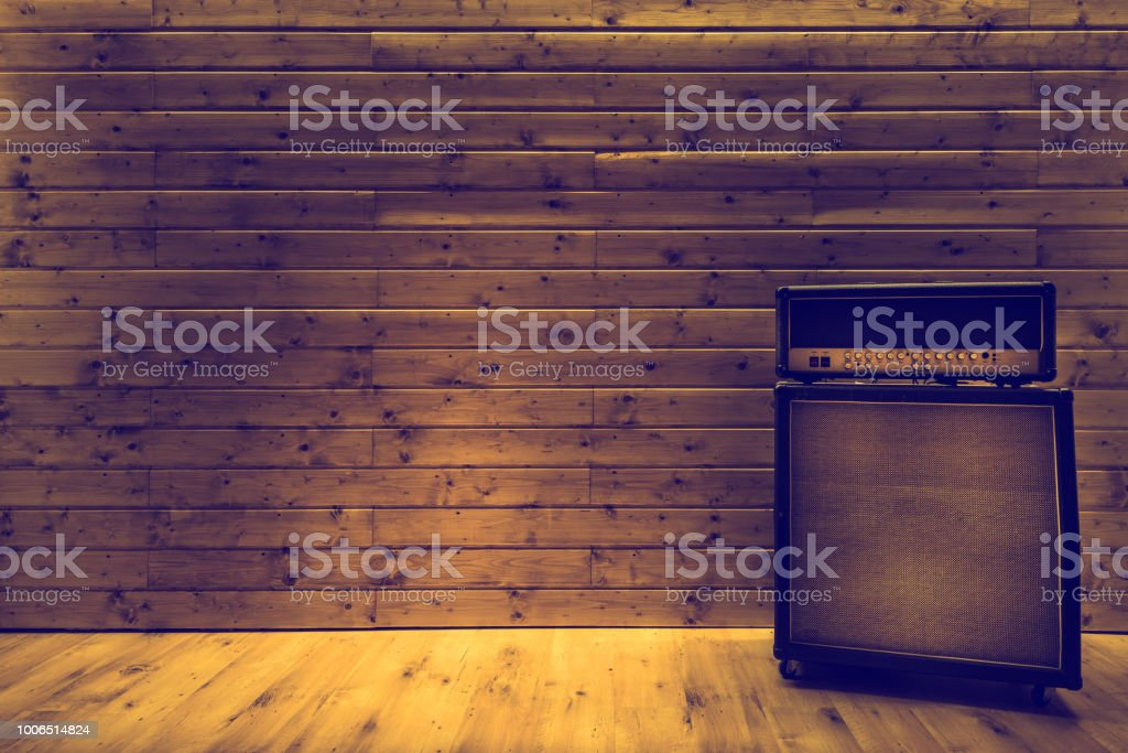 Guitar amplifier on wooden wall and floor, music studio stock photo