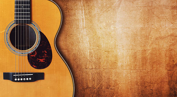 Guitar and blank grunge background Acoustic guitar resting against a blank grunge background with copy space folk music stock pictures, royalty-free photos & images