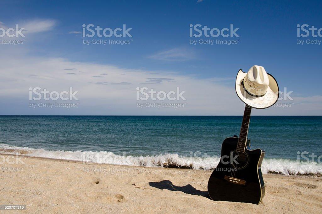La guitarra y sombrero de vaquero en la playa - foto de stock