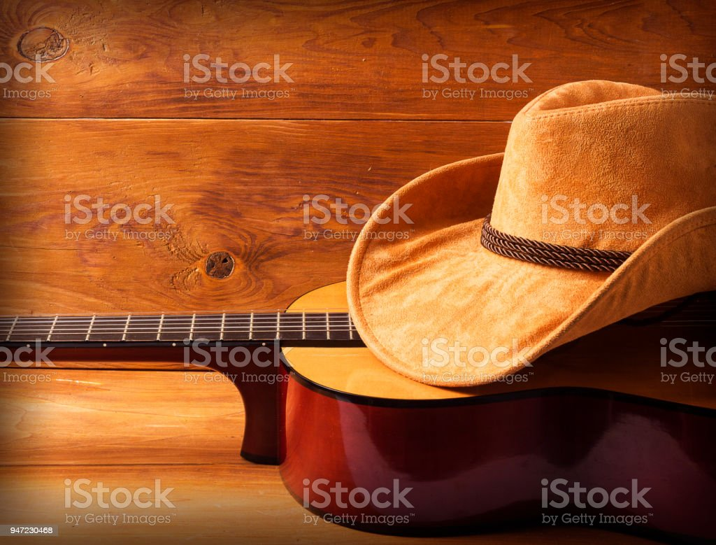Guitar and cowboy hat on wood background stock photo