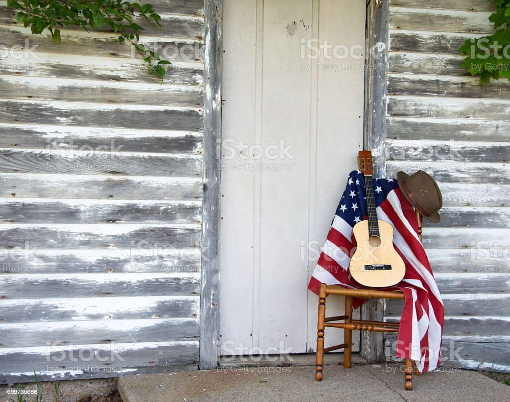 guitar and flag on wooden chair by door stock photo