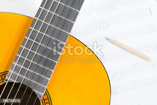 478117515 istock photo guitar and pencil on music sheet for composer 498704013
