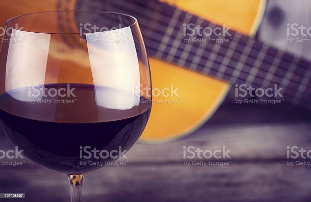 guitar and Wine on a wooden table stock photo