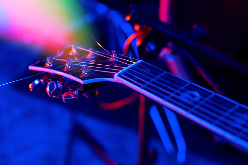 Guitar at the concert in colorful light.