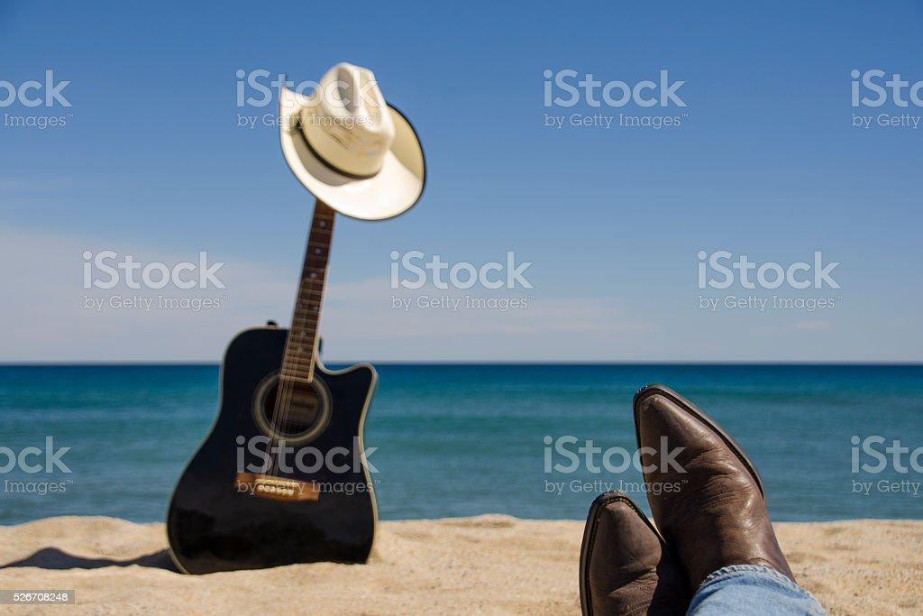 Guitarra, sombrero de vaquero y fundas en la playa - foto de stock