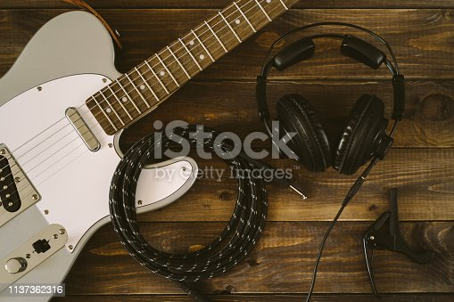 Guitar electric rock background. Headphones, cable jack and capo on wooden table, top view