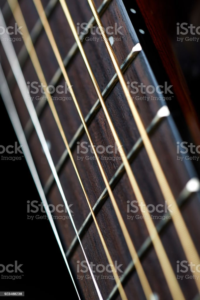 A guitar fretboard with strings on black background stock photo