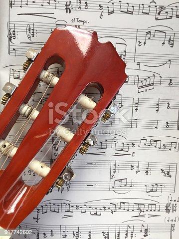 478117515 istock photo Guitar head on music sheet 917742602