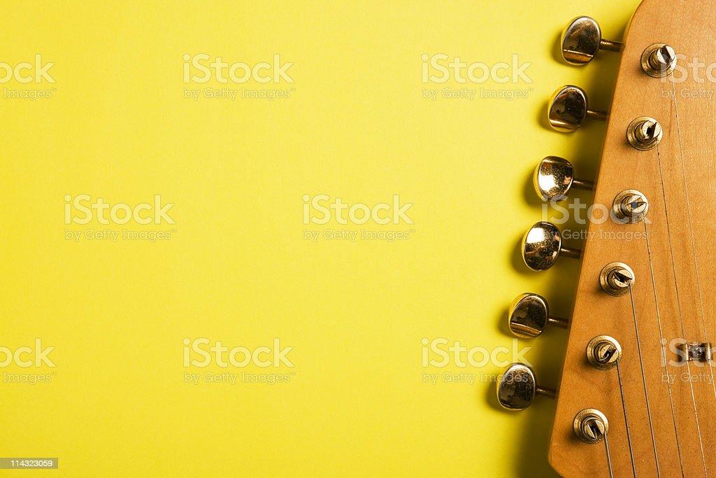Guitar headstock on yellow stock photo