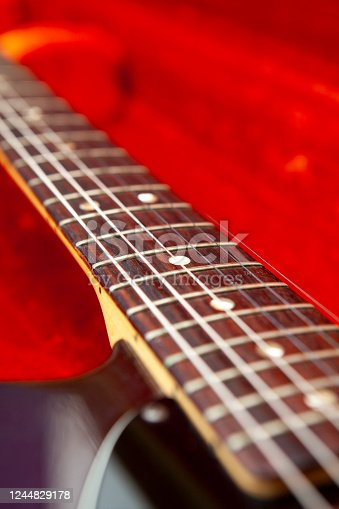Close-up of an electric guitar in a red fur lined guitar case with copy space