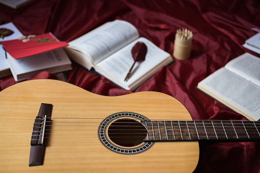 istock Guitar lying on red fabric, dried flowers, books on a red background, scattered books, fountain pen, art atmosphere 681568800