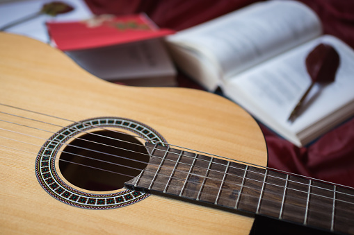 istock Guitar lying on red fabric, dried flowers, books on a red background, scattered books, fountain pen, art atmosphere 681586406