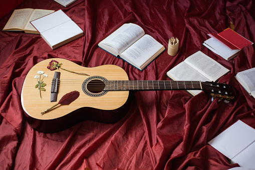 istock Guitar lying on red fabric, dried flowers, books on a red background, scattered books, fountain pen, art atmosphere 681886848