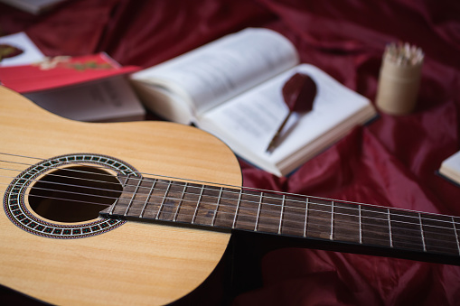istock Guitar lying on red fabric, dried flowers, books on a red background, scattered books, fountain pen, art atmosphere 681896240