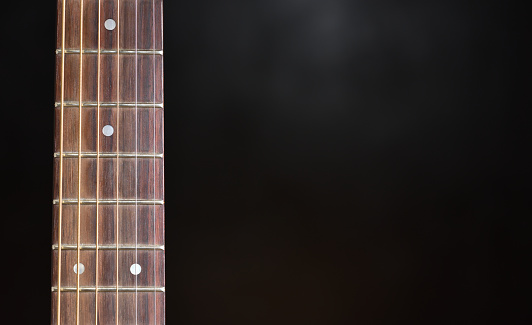 Guitar neck and strings close up on a black background