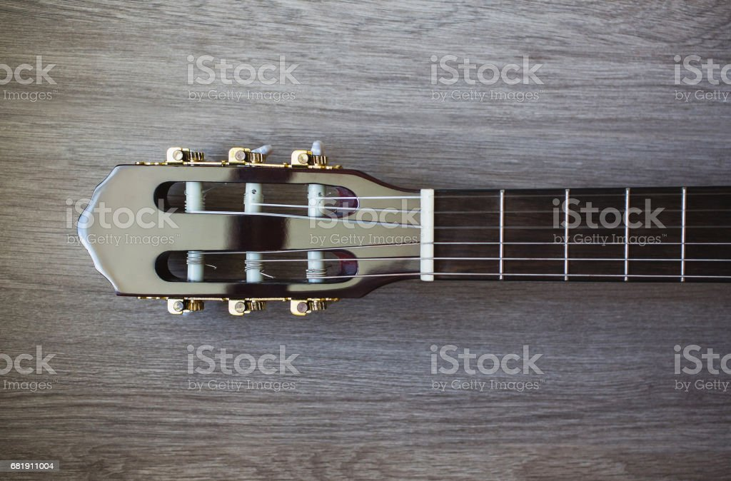 guitar neck on a wooden background, musical instrument, fretboard stock photo