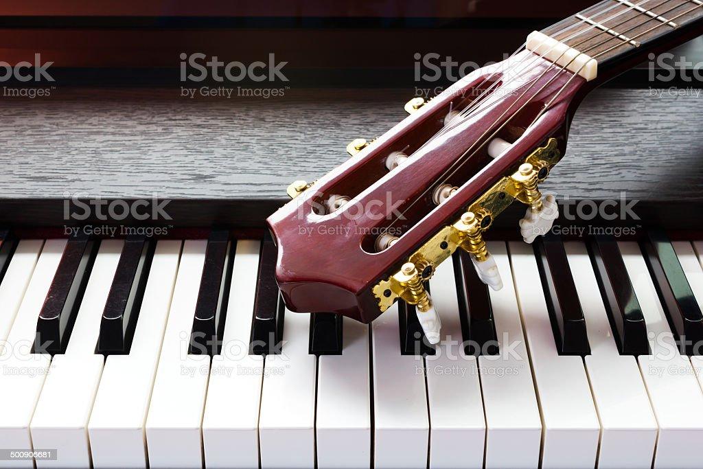 guitar neck on piano keys stock photo