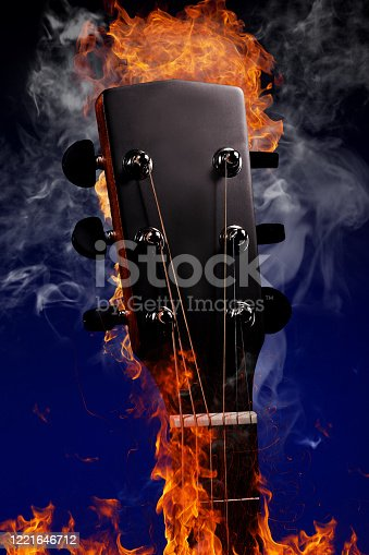 Guitar neck with strings in fire and smoke on a blue background. Advertising photo of a musical instrument with space for copying. Mockup