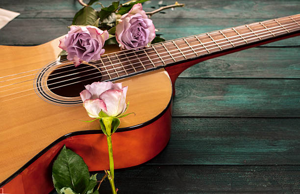 Guitar neck with tender pink roses on dark background A photo of a guitar neck with tender pink roses, on a dark wooden background with copyspace serenading stock pictures, royalty-free photos & images