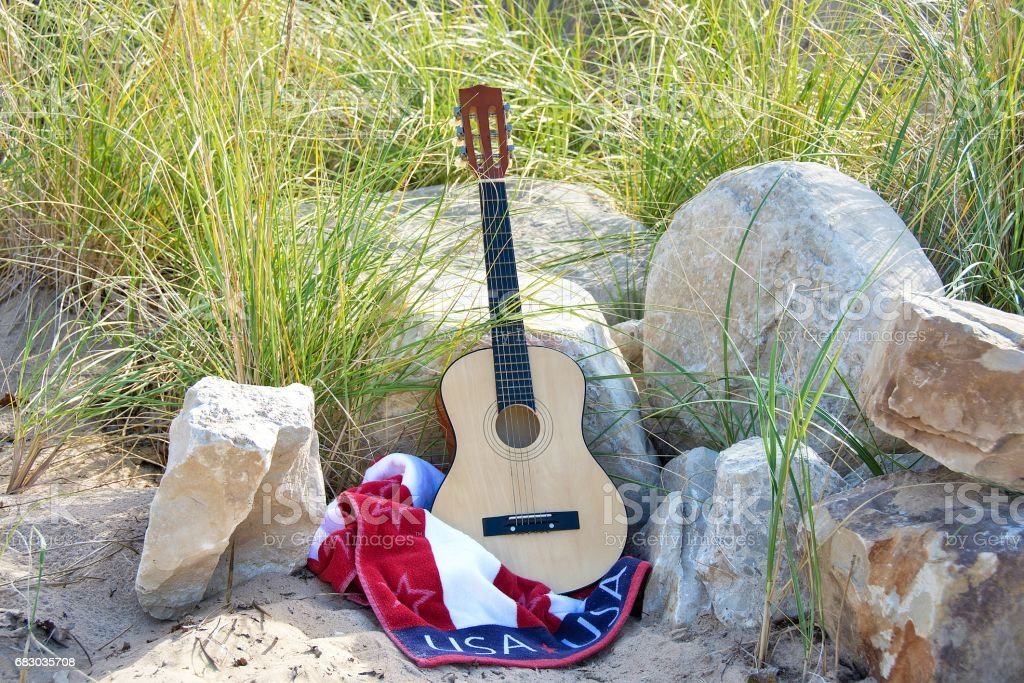guitar on beach rock with patriotic towel stock photo