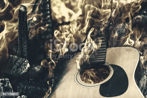 A stringless acoustic guitar is burning in a raging fire.
