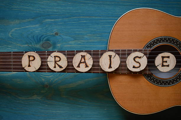 guitar on teal wood and the word: praise - praise and worship stock photos and pictures