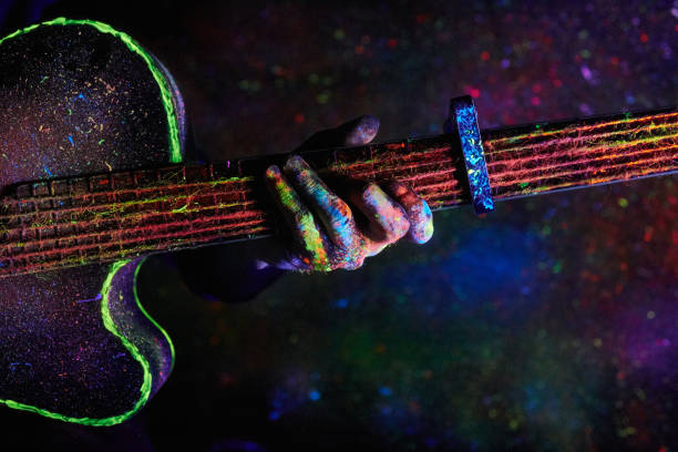 guitar painted with neon paint Christmas decoration. guitar painted with neon paint string instrument stock pictures, royalty-free photos & images
