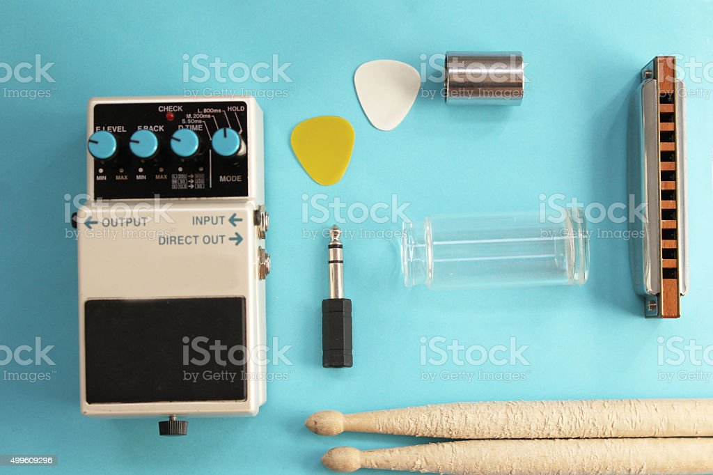Guitar pedal, drum sticks, harmonica, audio plug and guitar picks stock photo