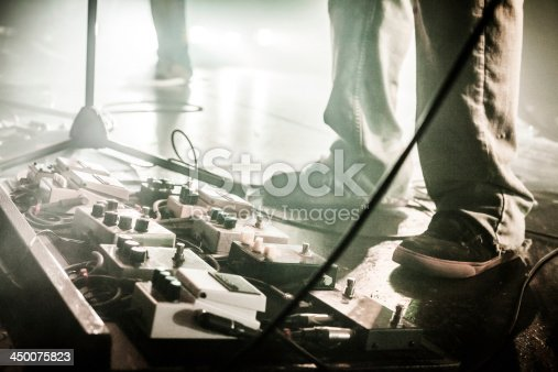 istock Guitar Pedals on stage with live band performing 450075823