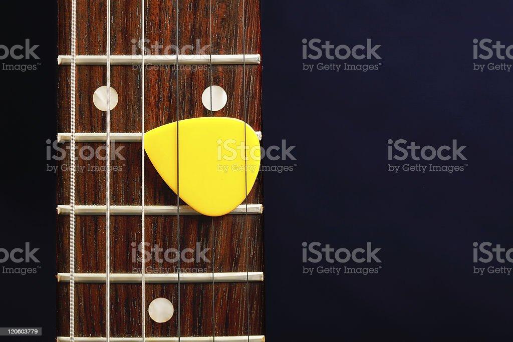 Guitar pick between strings stock photo