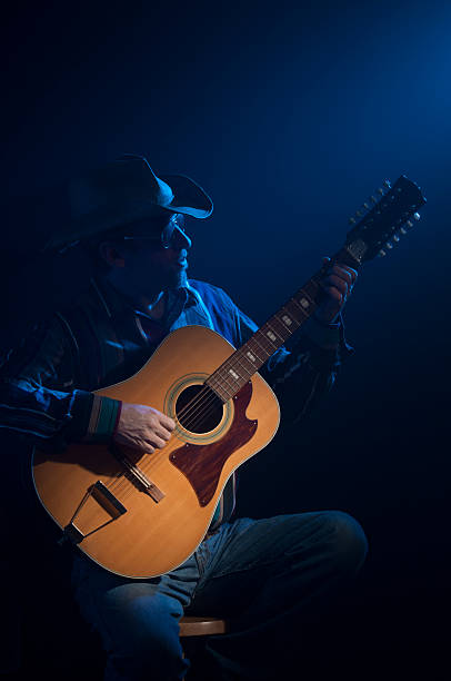 Guitar Country-Western guitar player against a dark background with spot light on the guitar. Blue accent light simulates stage appearance. country and western music stock pictures, royalty-free photos & images