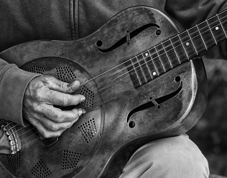 A detail picture of a guitar playing man with a metal - guitar. black abd White high contrast picture