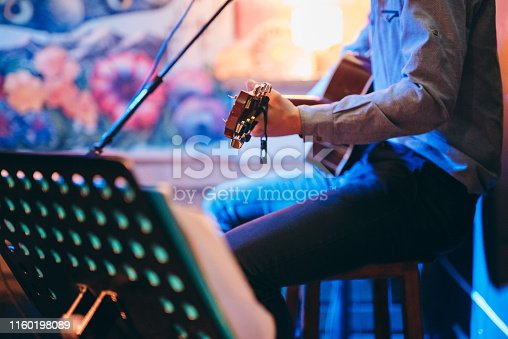 Guitar player in a café playing his music.