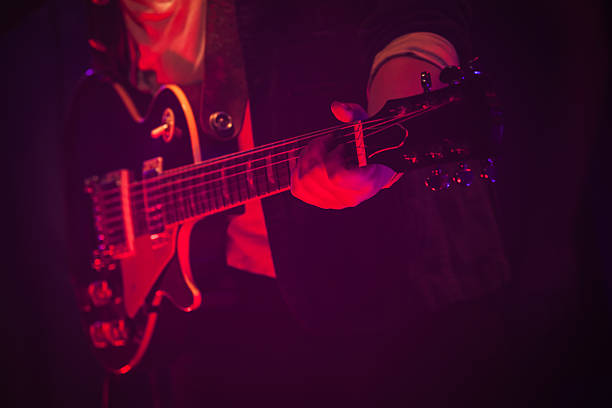 guitar player on a stage with red light - rock music stock pictures, royalty-free photos & images
