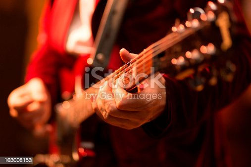 Guitar player fingers on guitar, available light, high iso shot, shallow depth of field