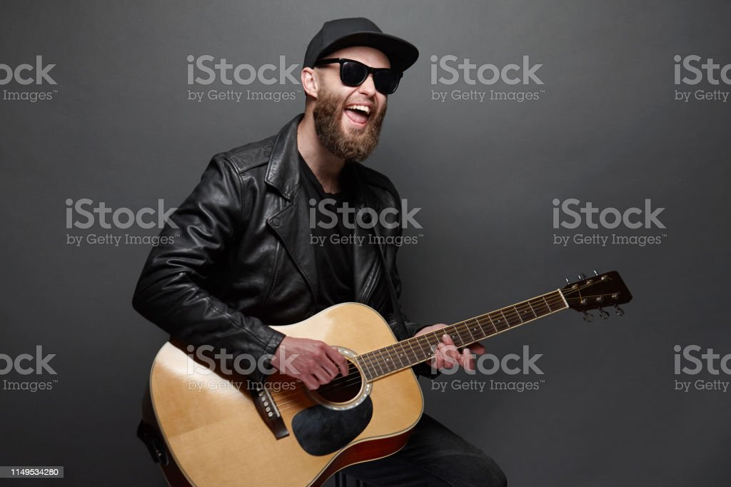 Guitar player singing in music studio. Hipster guitar player with...