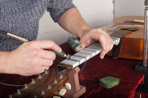 """gitarre-reparatur- und service - bünde arbeiter polieren gitarrenhals dremel """"und"""" einfügen goi - dremel zubehör stock-fotos und bilder"""